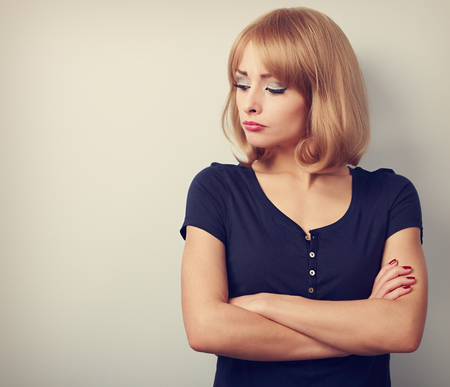 resentment: Resentful unhappy casual woman with short blond hair looking down. Toned closeup portrait