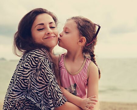 hugs and kisses: Cute kid girl kissing her happy enjoying mother with closed eyes and emotional face on sea background. Toned color portrait Stock Photo