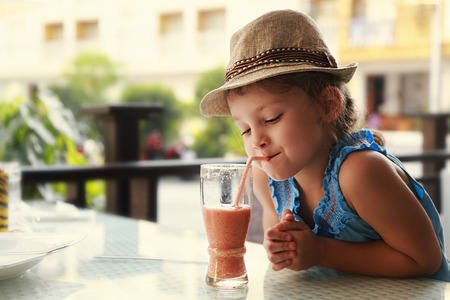 healthy smile: Cute thinking kid girl drinking tasty juice in street restaurant