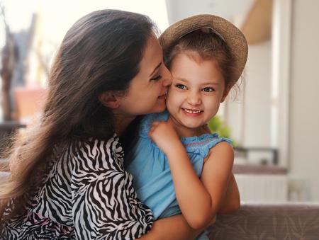 donna innamorata: Felice madre coccole e baciare la sua cute ragazza bambino in cappello