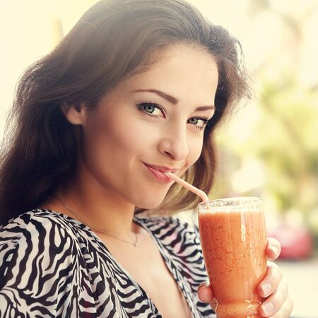 food and drink: Beautiful happy woman drinking smoothie juice on summer bright background. Closeup portrait