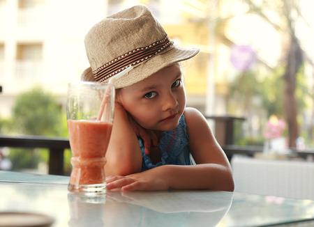 petite fille triste: enfant malheureux mignon assis dans le restaurant et pas envie de boire du jus sain sur fond d'�t�