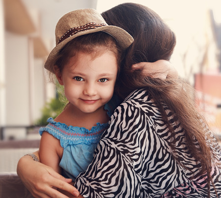 female portrait: Smiling kid girl embracing her beautiful mother outdoor summer background. Closeup toned portrait Stock Photo