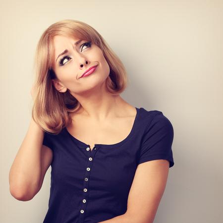 preguntando: Desconcertado infeliz mujer joven que piensa mirando hacia arriba sobre fondo vacío espacio de la copia. Tonificado retrato del primer