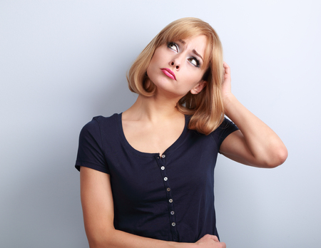 Puzzled stressed thinking young woman looking up on empty copy space and scratching the head