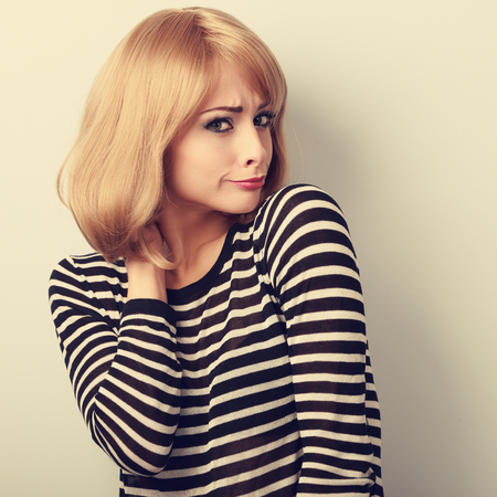 business skeptical: Displeased suspicious blond woman looking skeptical. Toned closeup portrait Stock Photo