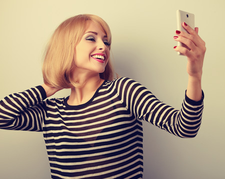 Funny cute blond woman making self photo of herself haircut and make-up on mobile phone. Toned closeup portrait Standard-Bild