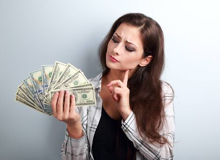 invest: Serious concentrated thinking business lady thinking where invest money and how to earing more dollars