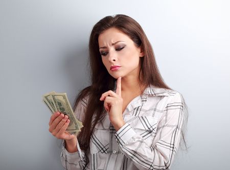 hand with money: Serious concentrated thinking business woman thinking where invest money and how to earing more dollars