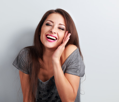 makeup eyes: Laughing makeup trendy woman with wide open mouth and closed eyes on blue background