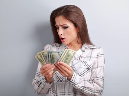 earned: Young surprising woman looking and counting her salary and thinking how little money she have earned and how she will pay to mortgage. It is economical crisis.