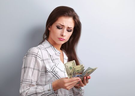 earned: Beautiful young unhappy woman looking on dollars and thinking how little money she have earned and how she will pay to mortgage Stock Photo
