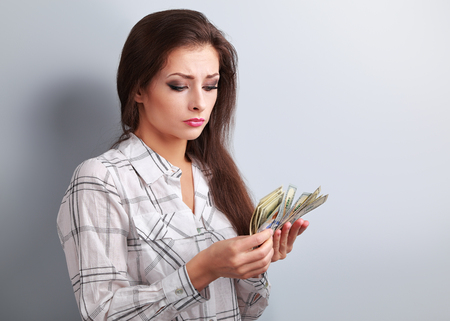 earned: Young serious woman looking and counting dollars and thinking how little money she have earned and how she will pay to mortgage. It is economical crisis. Stock Photo
