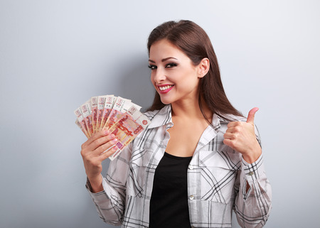roubles: Happy young casual woman in glasses holding roubles and showing thumb up sign with toothy smiling on blue background