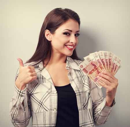 russian: Happy young casual woman in glasses holding roubles and showing thumb up sign with toothy smiling. Toned portrait Stock Photo
