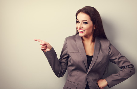 Beautiful happy business woman showing finger on something empty on copy space background. Toned portrait Stock Photo