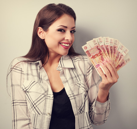 ruble: Happy young casual woman holding rubles with toothy smiling. Toned portrait Stock Photo