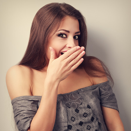 big mouth: Surprise makeup woman cover mouth the hand and looking with big eyes. Toned closeup portrait Stock Photo