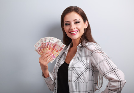 ruble: Happy young casual woman holding rubles with toothy smiling on blue background