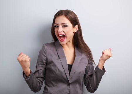 excited woman: Excited winner business woman with opened mouth. Happy young satisfacted female showing the gesture yes by fists on blue background