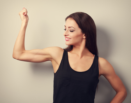 woman muscle: Strong fitness young woman showing muscle bicep with happy smiling. Toned portrait