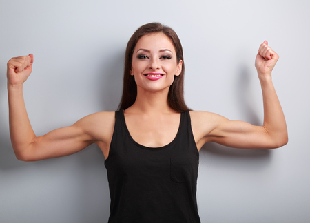 woman muscle: Pleased strong fit woman showing muscle biceps with happy smiling on blue background