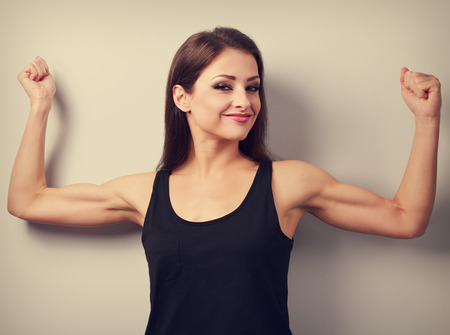 flexing: Pleased strong young woman showing muscle biceps with smiling. Toned closeup portrait