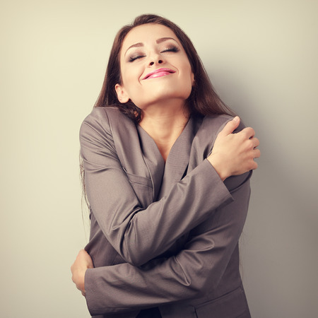 egoist: Happy business woman hugging herself with natural emotional enjoying face. Love concept of yourself. Toned portrait