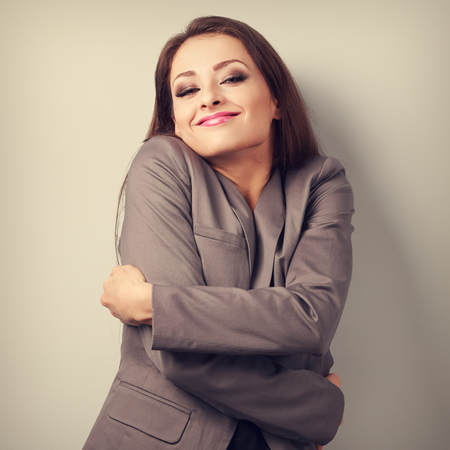 fulfilled: Enjoying business woman hugging herself with natural emotional face. Love concept of yourself. Toned portrait
