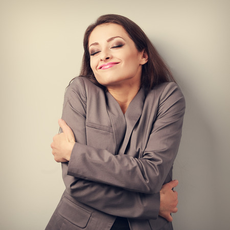fulfilled: Happy business woman hugging herself with closed eyes and natural emotional face. Love concept of yourself. Toned portrait Stock Photo