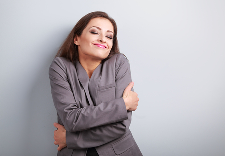 yourself: Happy business woman hugging herself with closed eyes and natural emotional face. Love concept of yourself Stock Photo