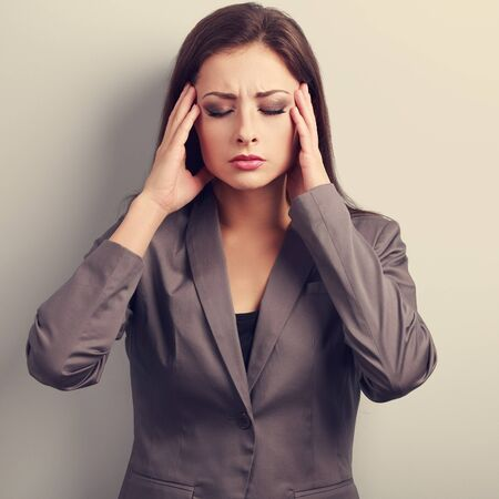 stressed business woman: Unhappy stressed business woman in suit holding head the hands. Toned portrait Stock Photo