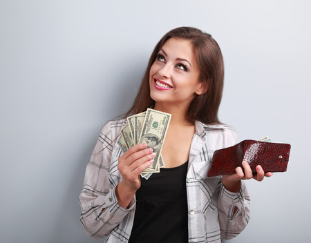 spent: Happy smiling woman holding wallet and dollars and thinking how to spent its on blue background Stock Photo