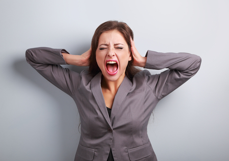 bitchy: Angry business woman in suit strong screaming with wild open mouth and holding head the hands. Closeup portrait on blue background