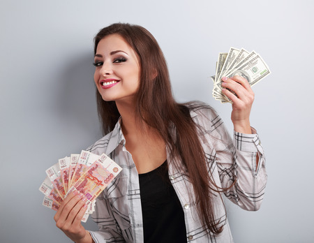 Happy business woman thinking that currency to choose, dollars or rubles and choosing dollars holding money in different hands on blue background