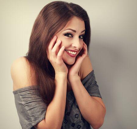 mouth smile: Happy laughing brunette young woman holding the hand at face and giggling. Toned closeup portrait Stock Photo