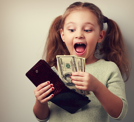 Cute surprising kid girl holding wallet and looking on dollars with open mouth and think how can to spend so much money. Happy childhood. Toned closeup portrait