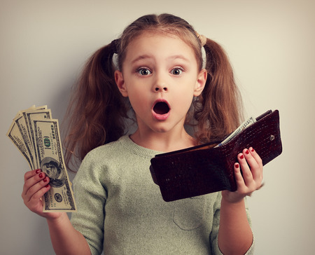 Cute surprising kid girl holding wallet and dollars with open mouth and think how can to spend so much money. Happy childhood. Toned closeup portrait Imagens