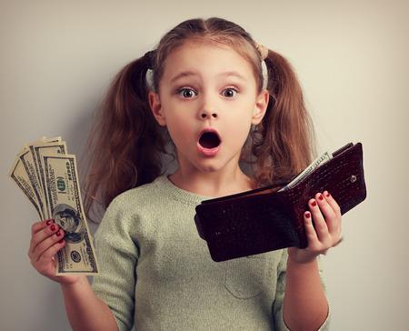 Leuk verrassend jong meisje bedrijf portemonnee en dollars met open mond en denken hoe kan zoveel geld uit te geven. Gelukkige jeugd. Afgezwakt close-up portret