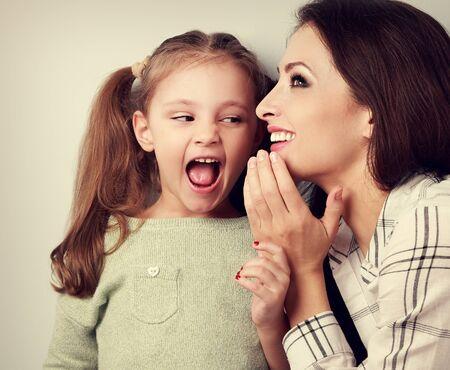 Madre felice sussurrando il segreto per la sua sorprendente ragazza carina in orecchio su sfondo blu