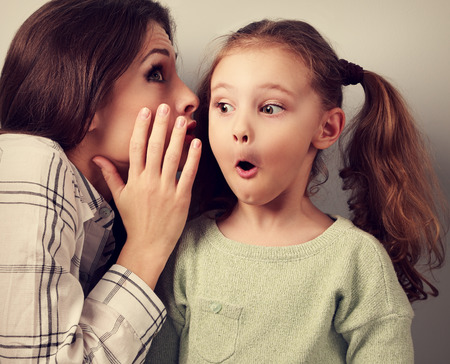 talk: Shocked mother whispering the secret information to her surprising cute girl in ear on blue background
