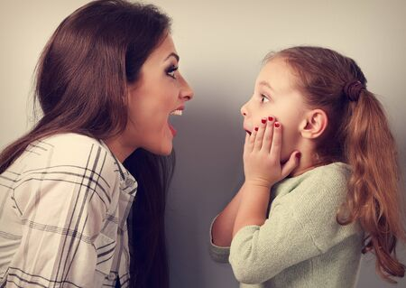 wonder: Excited mother and surprising kid girl looking on each other with opened mouth. Toned vintage portrait Stock Photo