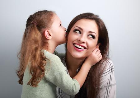 Heureux mignon enfant fille chuchoter le secret de sa mère souriante dans l'oreille avec le visage amusant sur fond bleu