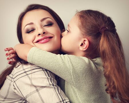 hugs and kisses: Cute kid girl kissing and cuddling her enjoying beautiful mother in studio. Toned closeup portrait of family love. Stock Photo