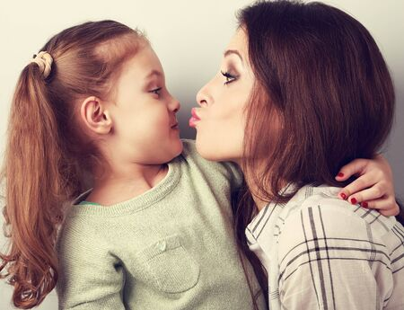 comical: Funny amusing young mother wanting to kiss her comical grimacing daughter. Toned closeup portrait Stock Photo