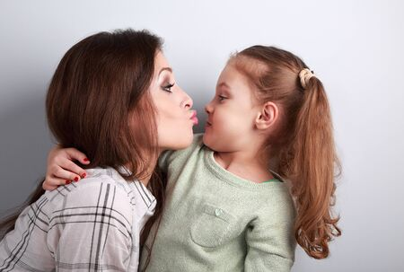 Funny amusing young mother wanting to kiss her comical grimacing daughter in studio