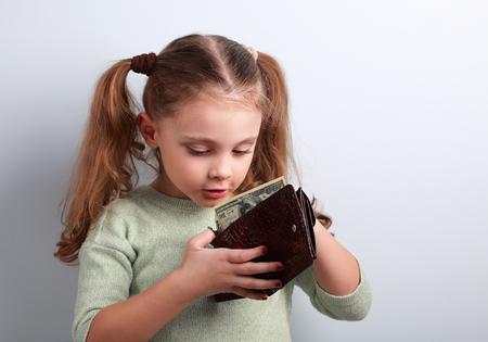 money concept: Cute surprising small kid girl looking in mother wallet and want to take money with empty copy space Stock Photo