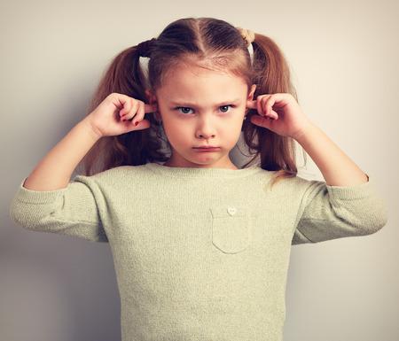 Enojado infeliz muchacha niño oídos coverd los dedos y haciendo un gesto que no quiere escuchar. retrato entonado de la vendimia