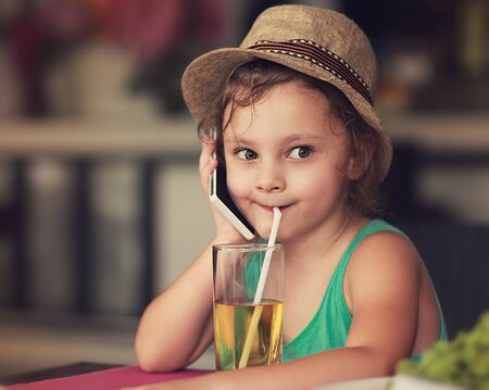 tomando jugo: Fun happy kid girl talking on mobile phone and drinking apple juice in cafe. Toned closeup portrait Foto de archivo