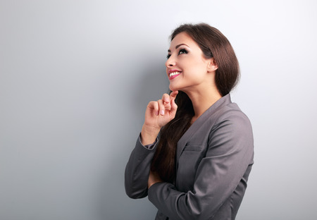 Happy young business woman in suit thinking and looking on empty copy space Stock Photo